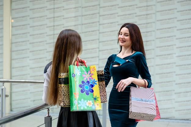 Mooie en gelukkige meisjes winkelen in het winkelcentrum.