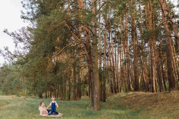 Mooie en gelukkige moeder en dochter die een goede tijd in het bos hebben