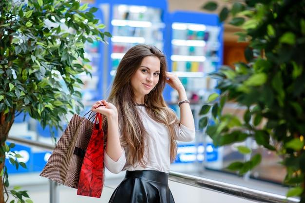Mooie en gelukkige vrouw die boodschappen doet in het winkelcentrum