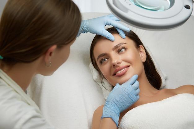 Mooie en gelukkige vrouw die lacht naar cosmetologie arts bij schoonheidskliniek