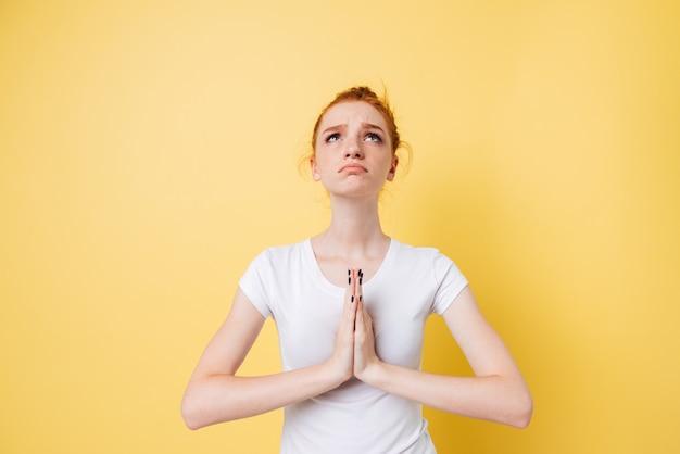 Mooie en gembervrouw die omhoog bidt kijkt