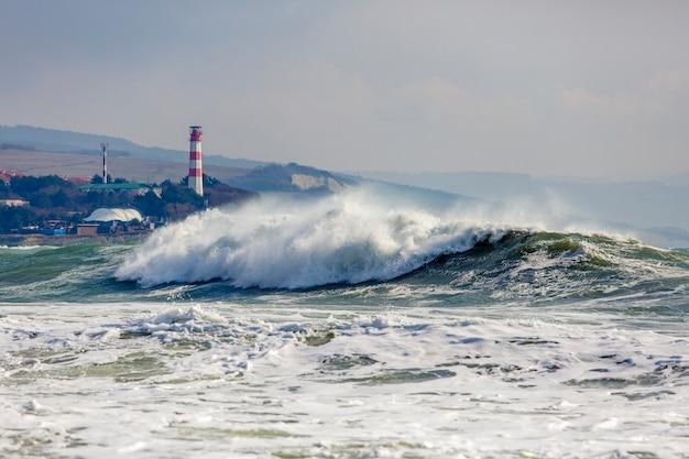 Mooie en gevaarlijke stormgolven op de achtergrond van de gelendjik vuurtoren. resort gelendzhik, kaukasus, steile rotsachtige kust.