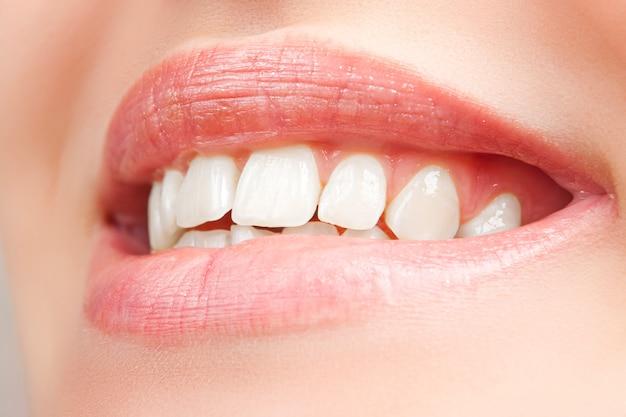 Mooie en gezonde vrouw glimlach, close-up geïsoleerd op een witte achtergrond