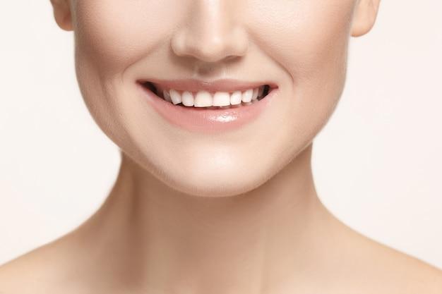 Mooie en gezonde vrouwenglimlach, close-up op witte achtergrond