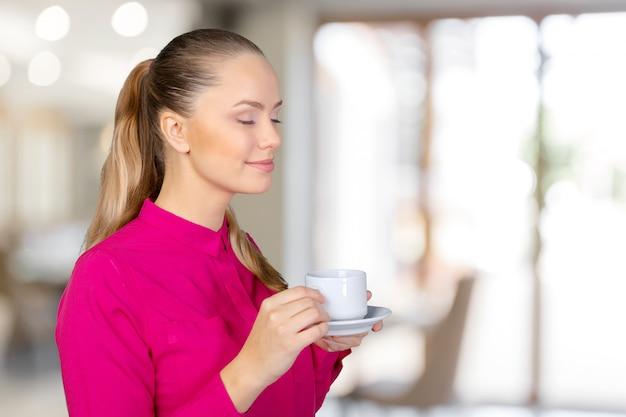 Mooie en glimlachende vrouw met een kopje koffie