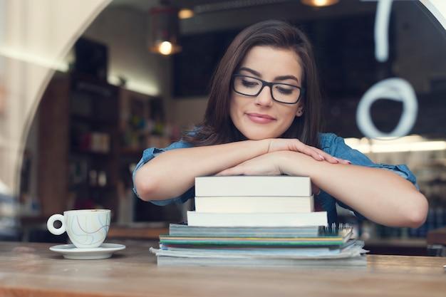 Mooie en glimlachende vrouwelijke student bij café