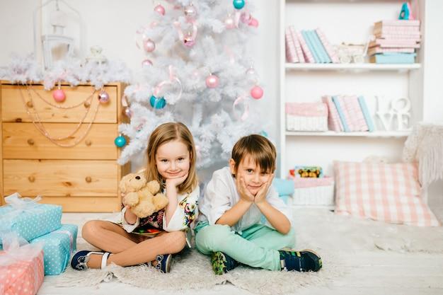 Mooie en grappige kinderen poseren voor de camera in een kamer met nieuwe jaar vakantie decoraties.