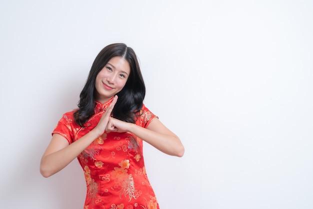 Mooie en jonge aziatische vrouw draagt ?? rode chinese traditionele kleding en glimlacht voor chinees nieuwjaar op witte achtergrond