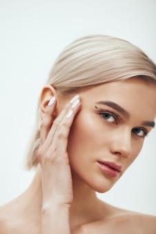 Mooie en jonge blonde vrouw die haar gezicht aanraakt met zwarte chirurgische lijnen op de oogleden en