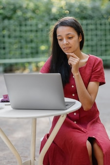 Mooie en jonge duizendjarige afrikaanse vrouw op een openbare plek die op een laptop werkt