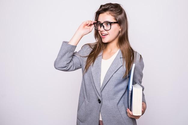 Mooie en jonge student met grote glazen dichtbij sommige boeken die op witte achtergrond glimlachen