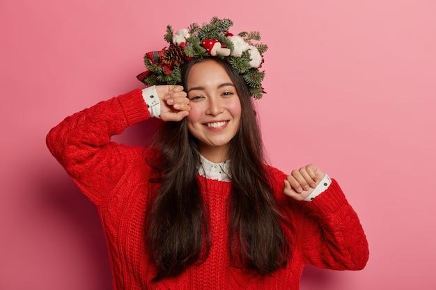 Mooie en jonge vrouw die de kroon van kerstmis op haar hoofd draagt