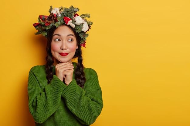 Mooie en jonge vrouw die de kroon van kerstmis op haar hoofd draagt Gratis Foto