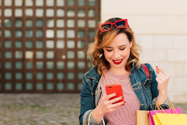 Mooie en jonge vrouw die naar haar telefoon kijkt tijdens het winkelen in de zomerverkoop, met veel kleurrijke tassen.