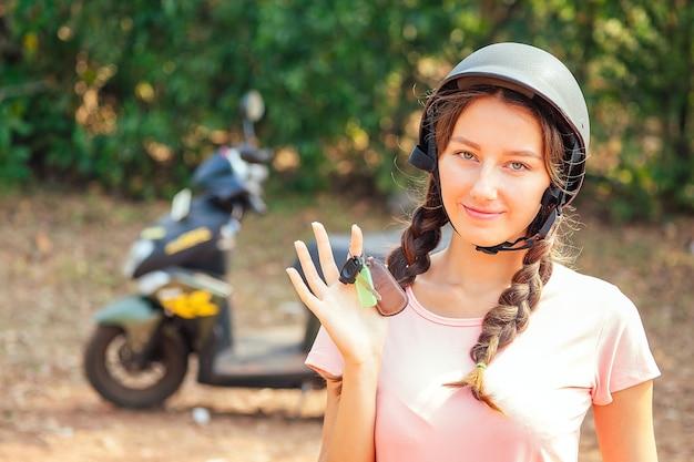 Mooie en jonge vrouw in een veiligheidshelm zittend op een motorfiets fiets en houdt de sleutels. concept van veilig scooter rijden en huren in azië.
