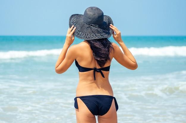 Mooie en jonge vrouw in een zwart badpak en een zwarte hoed op het strand. vakantie in een tropisch land.
