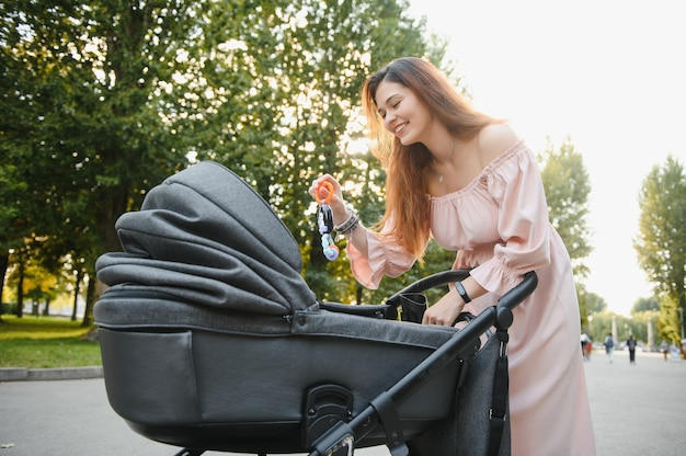 Mooie en jonge vrouw moeder en baby in een kinderwagen wandelen in het park
