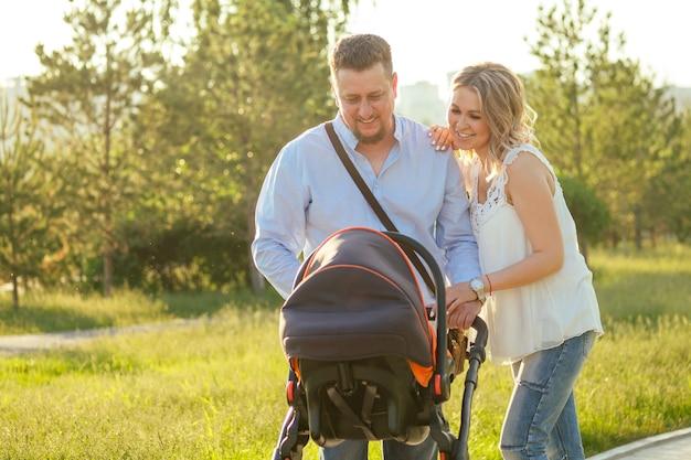 Mooie en jonge vrouw moeder knappe man en baby in een kinderwagen wandelen in het park.