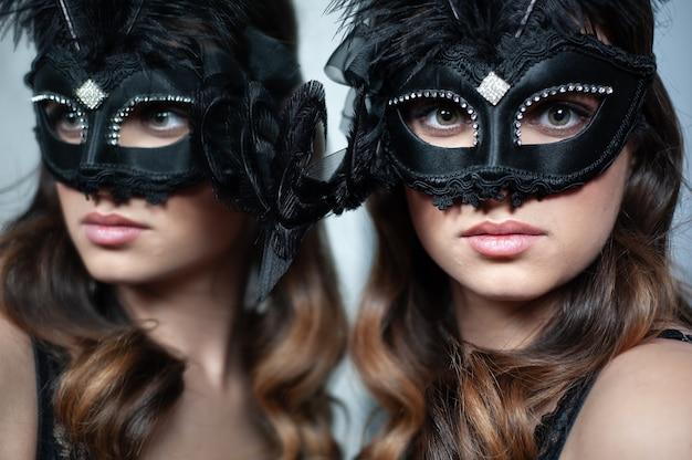 Mooie en jonge vrouw poseren in sexy lingerie en venetiaans masker
