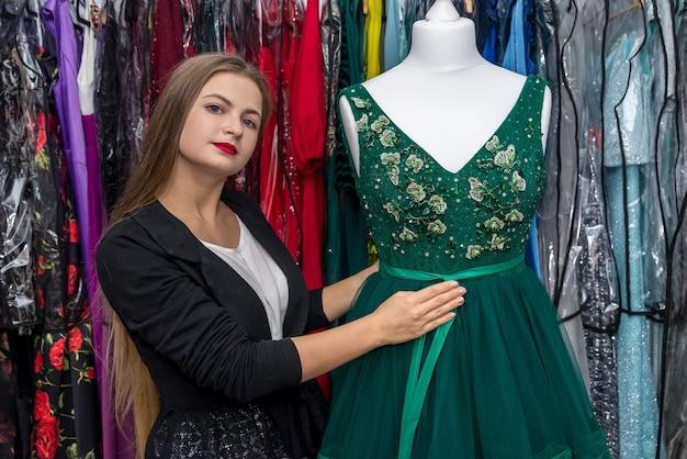 Mooie en jonge vrouw poseren met jurk op mannequin