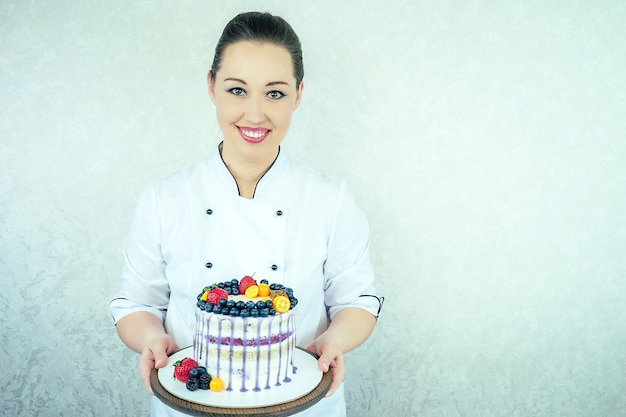 Mooie en lachende vrouw banketbakker in wit werk uniform siert de taart in de keuken. banketbakker, cake, koken. bruiloft en verjaardagstaart met bessen.