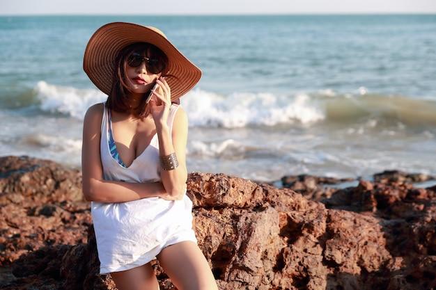 Mooie en leuke zakenvrouw met behulp van mobiele telefoon met zonnebril en hoed op het strand tijdens vakantievakantie