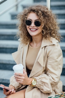 Mooie en modieuze jonge vrouw met boodschappentassen die op straat in de stad zit en over de schouder kijkt.