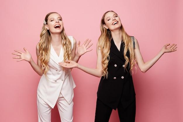 Mooie en modieuze tweeling, twee vrolijke en lachende blonde jonge model meisjes in mouwloze jassen en broeken, geïsoleerd op roze achtergrond