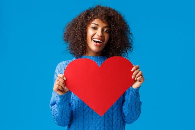 Mooie en schattige afro-amerikaanse mooie vrouw met afro-kapsel, met valentijnsdagkaart, groot hart en glimlachen, liefde en genegenheid uiten, ware gevoelens tonen, soulmate zoeken