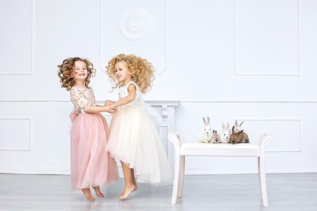 Mooie en schattige kleine meisjeskinderen in de trendy vakantiejurken met dierenkonijnen