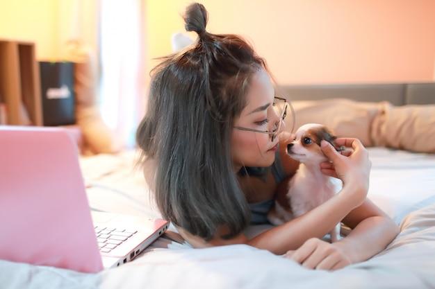 Mooie en sexy vrouw met behulp van mobiele telefoon en spelen met schattige puppy hond op bed