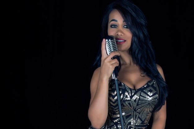 Mooie en sexy zwarte zangeres in een zilver getailleerde jurk met een retro stijl