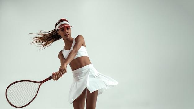 Mooie en slanke jonge afrikaanse vrouw in sportkleding die tennis speelt in de studio tegen een grijze achtergrond. tennisconcept. professionele sport