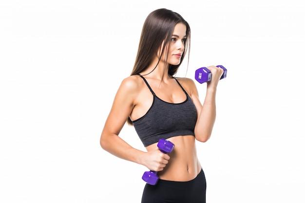 Mooie en sportieve jonge vrouw die gewichten opheft tegen wit.