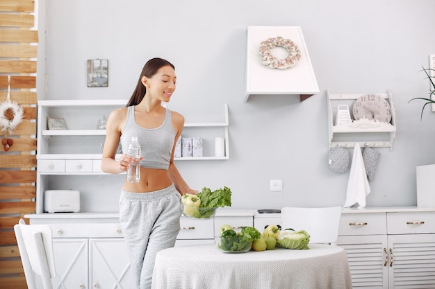 Mooie en sportieve vrouw in een keuken met groenten