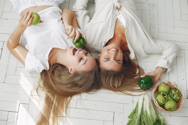 Mooie en sportieve vrouwen in een keuken met groenten