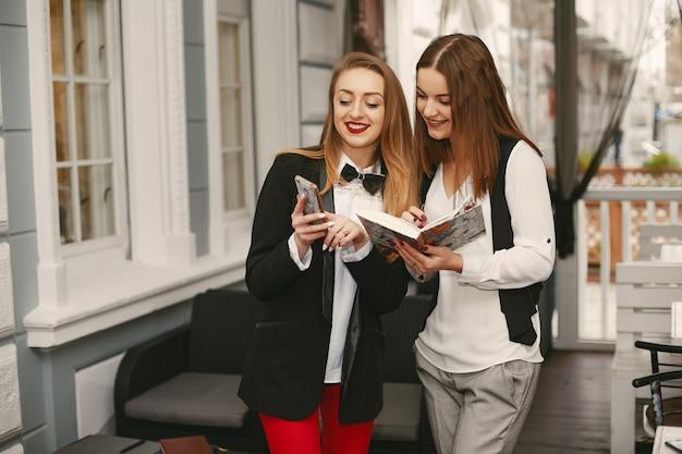 Mooie en stijlvolle jonge ondernemers permanent met telefoon in een cafe en werken