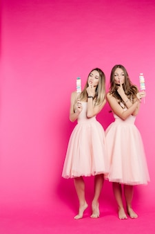 Mooie en stijlvolle meisjes met marshmallow snoepjes op stok.
