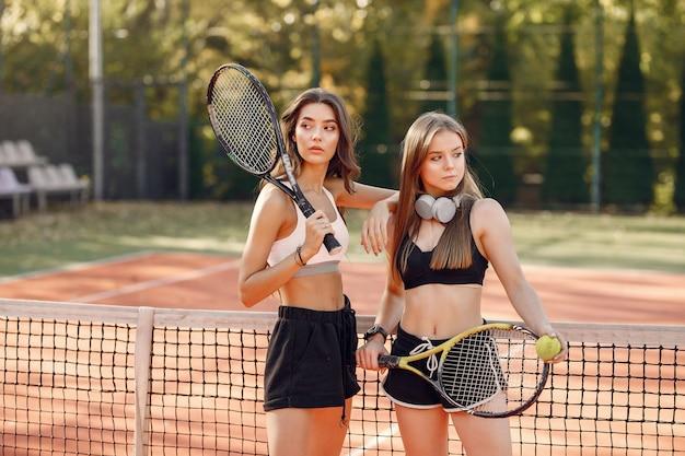 Mooie en stijlvolle meisjes op de tennisbaan