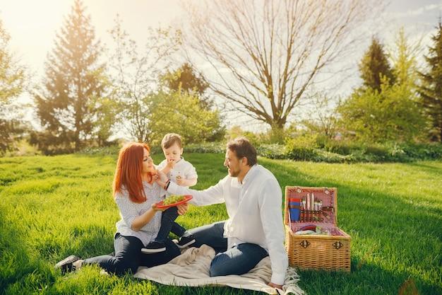 Mooie en stijlvolle roodharige moeder in een witte blouse zit op het gras met haar mooie man
