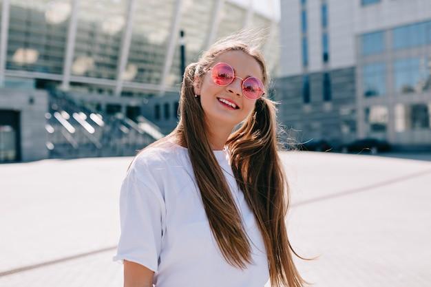 Mooie en stijlvolle tiener loopt op zonnige straat en draagt een roze zonnebril