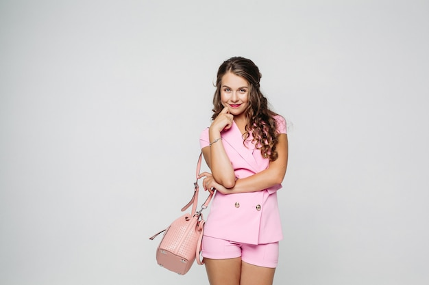Mooie en stijlvolle vrouw die in het roze kostuum stellen bij studio draagt.