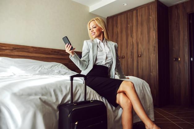 Mooie en succesvolle vrouw in formele kleding zit op het bed in een hotelkamer en gebruikt een telefoon