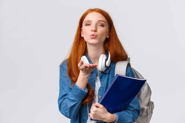 Mooie en tedere, sensuele roodharige studente, brutale student met rood kapsel, luchtkus sturen, hartstochtelijk mwah naar de camera blazen, rugzak en map met documenten vasthoudend.