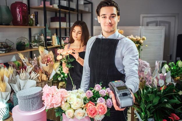Mooie en vrolijke jonge mannelijke bloemist kijken en houden therminal geld. hij staat aan tafel met bloemen. de jonge vrouw is achter hem die boeket maakt.