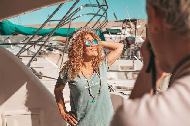 Mooie en vrolijke volwassen blanke vrouw lacht en veel plezier met fotograaf op de boot