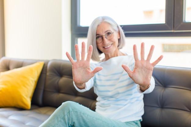 Mooie en vrouw van middelbare leeftijd die vriendelijk glimlacht kijkt, nummer tien of tiende met vooruit hand toont, aftellend