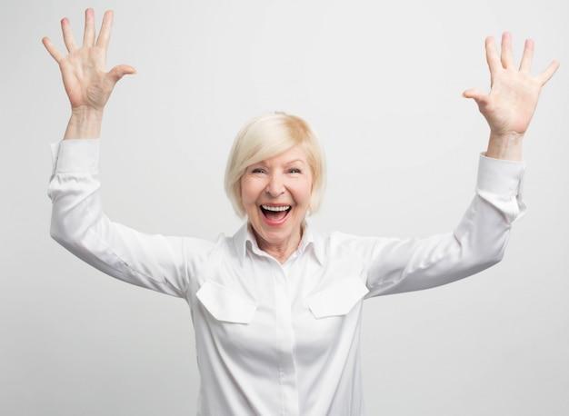 Mooie en vrouwelijke oude vrouw die high-five met beide handen toont. ze is blij en verrast. deze vrouw ziet er zelfverzekerd uit.