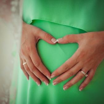 Mooie en zachte zwangere buik en handen van de vrouw erop