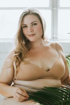 Mooie en zelfbewuste plus size vrouw in naakt ondergoed